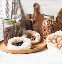round glass jar on wooden serving board with dry bulk grocery nets along a wooden serving board in plastic free kitchen